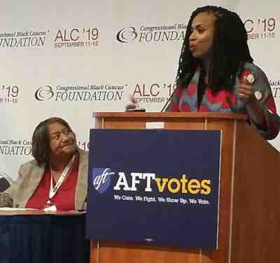 A black woman, Ayanna Pressley, speaks at a podium while an older black woman, Lorretta Johnsom, looks at her.