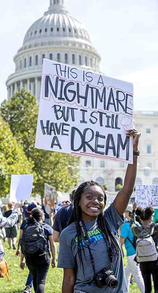 a girl holds a sign that says 'this is a nightmare but I still have a dream'