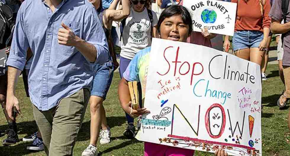 young girl holds a sign that says 'stop climate change now!'