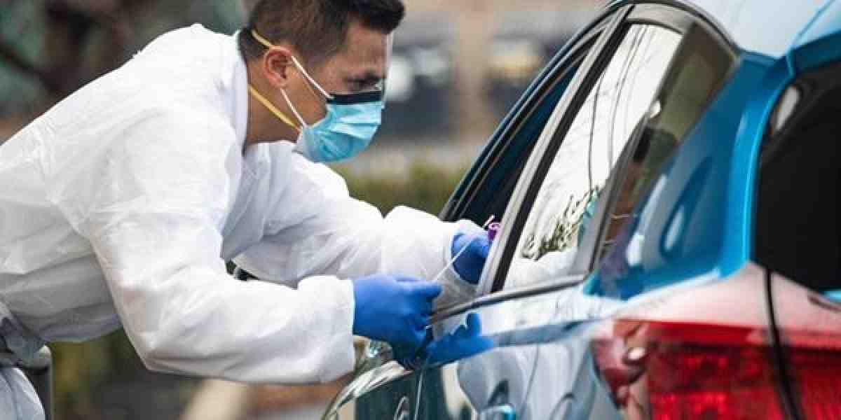 man in protective gear greets car at coronavirus testing site