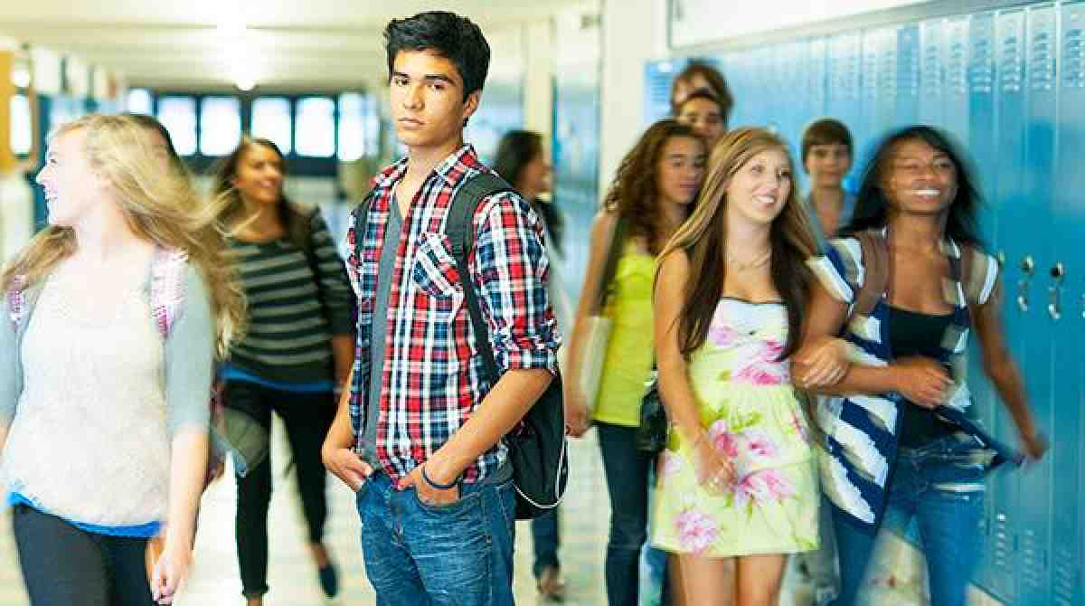 young man in high school hallway with blurry students in background