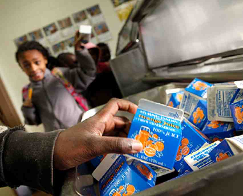 small cartons of orange juice and an adult african american hand in the foreground, and a small african american child holding a carton is in the background