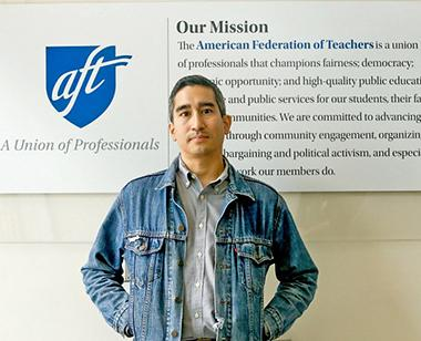 "A man, Jose Brito, stands in front of the AFT's ""Our Mission"" sign."