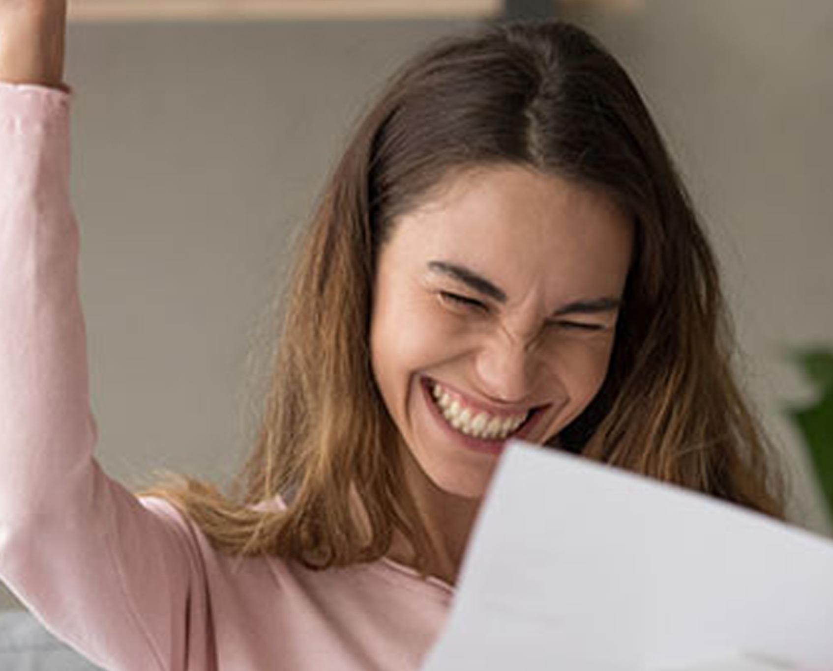 woman smiles in celebration as she looks at piece of paper