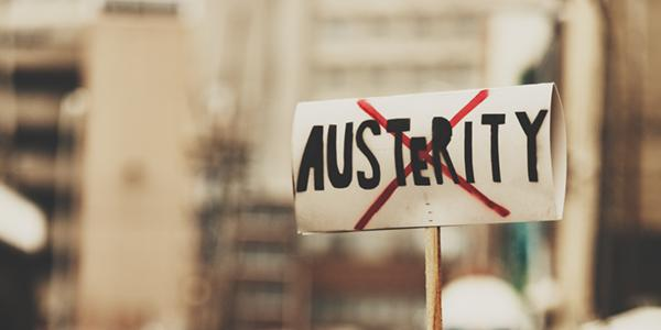 a protest sign has the word austerity on it with a red x over it
