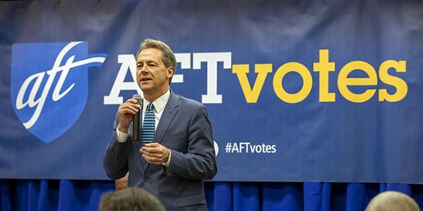 Governor Bullock speaks in front of an 'AFT votes' sign
