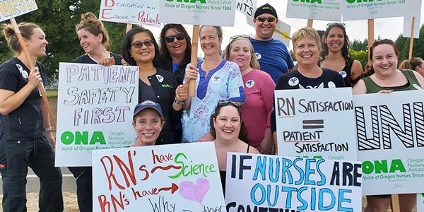 nurses stand with signs