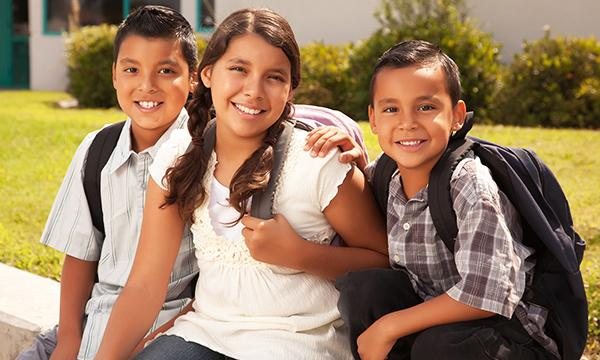 three latinx children smile while wearing backpacks
