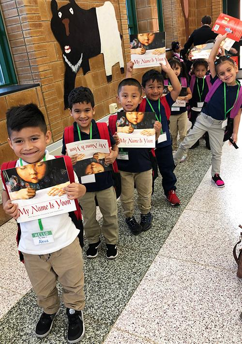 a line of small latino children pose for a picture with their books. they are smiling.