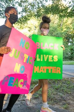 "Youths hold signs reading ""No Justice No Peace"" and ""Black Lives Matter"""