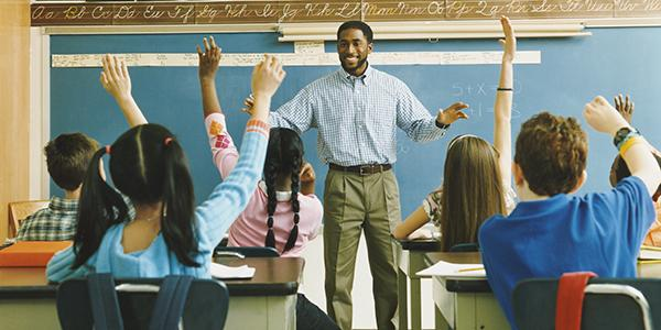 black teacher stands in front of his class. the children raise their hands