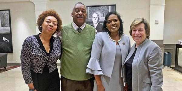 a group of three black people stand with a white woman