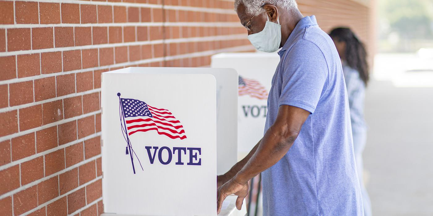 man in a mask votes at a voting booth