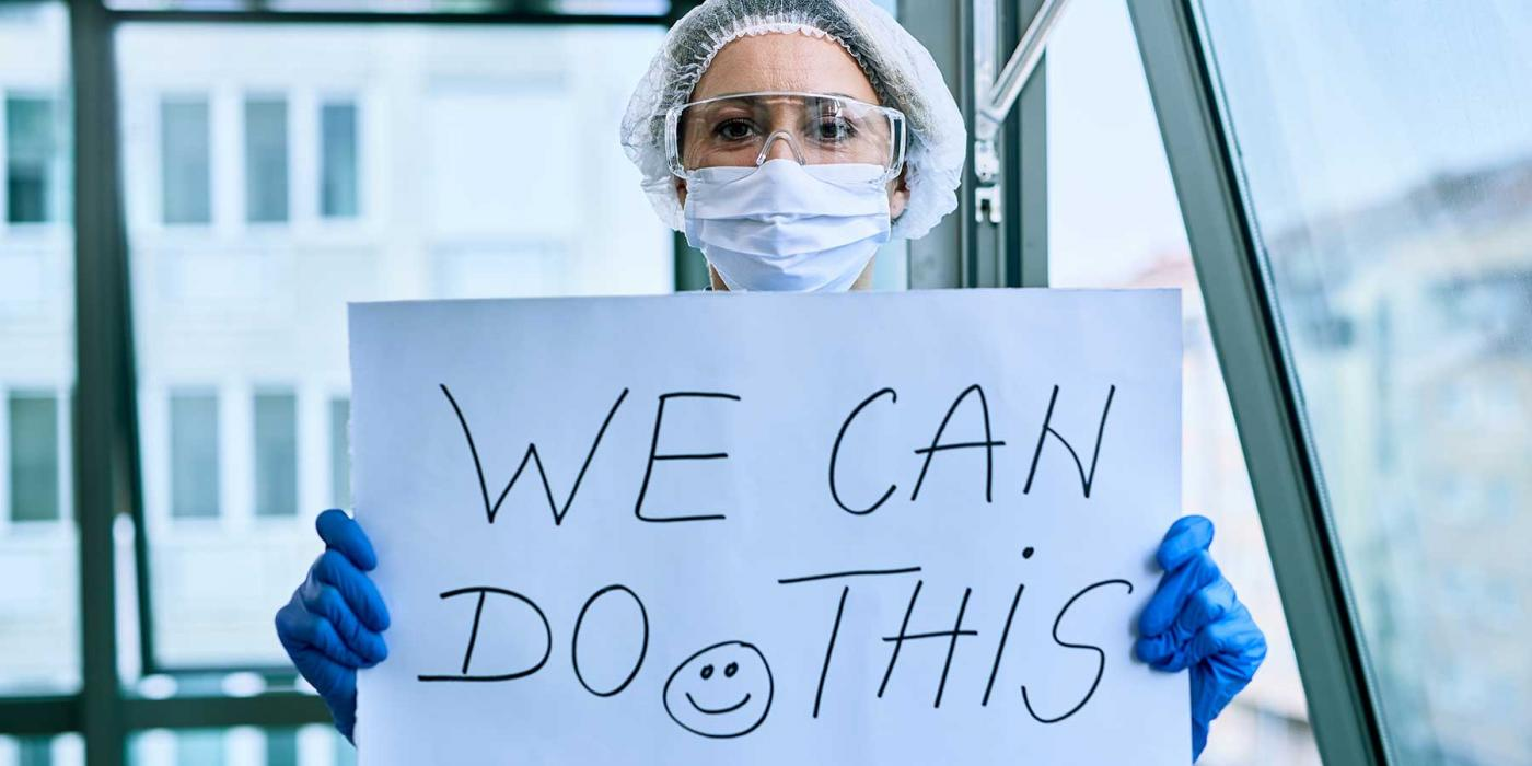a healthcare work in ppe holds a sign that says we can do this