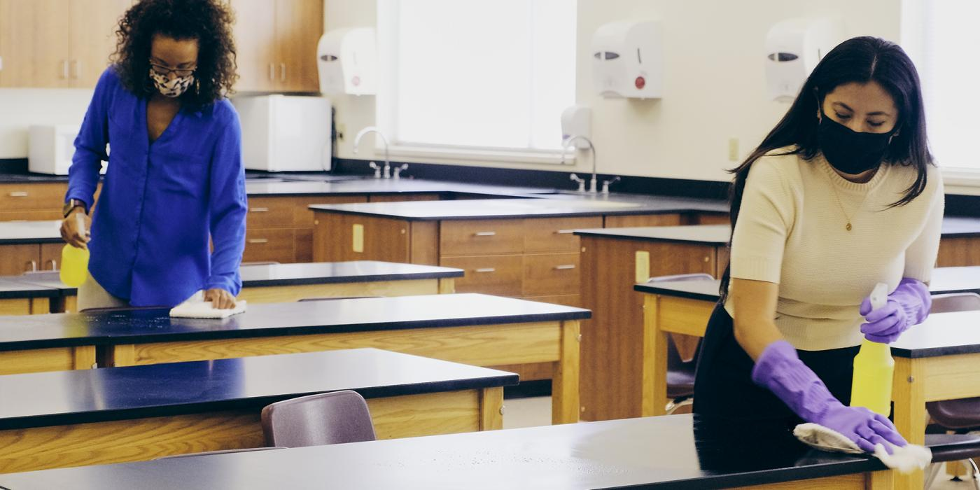 teachers with mask and gloves on disinfect desks