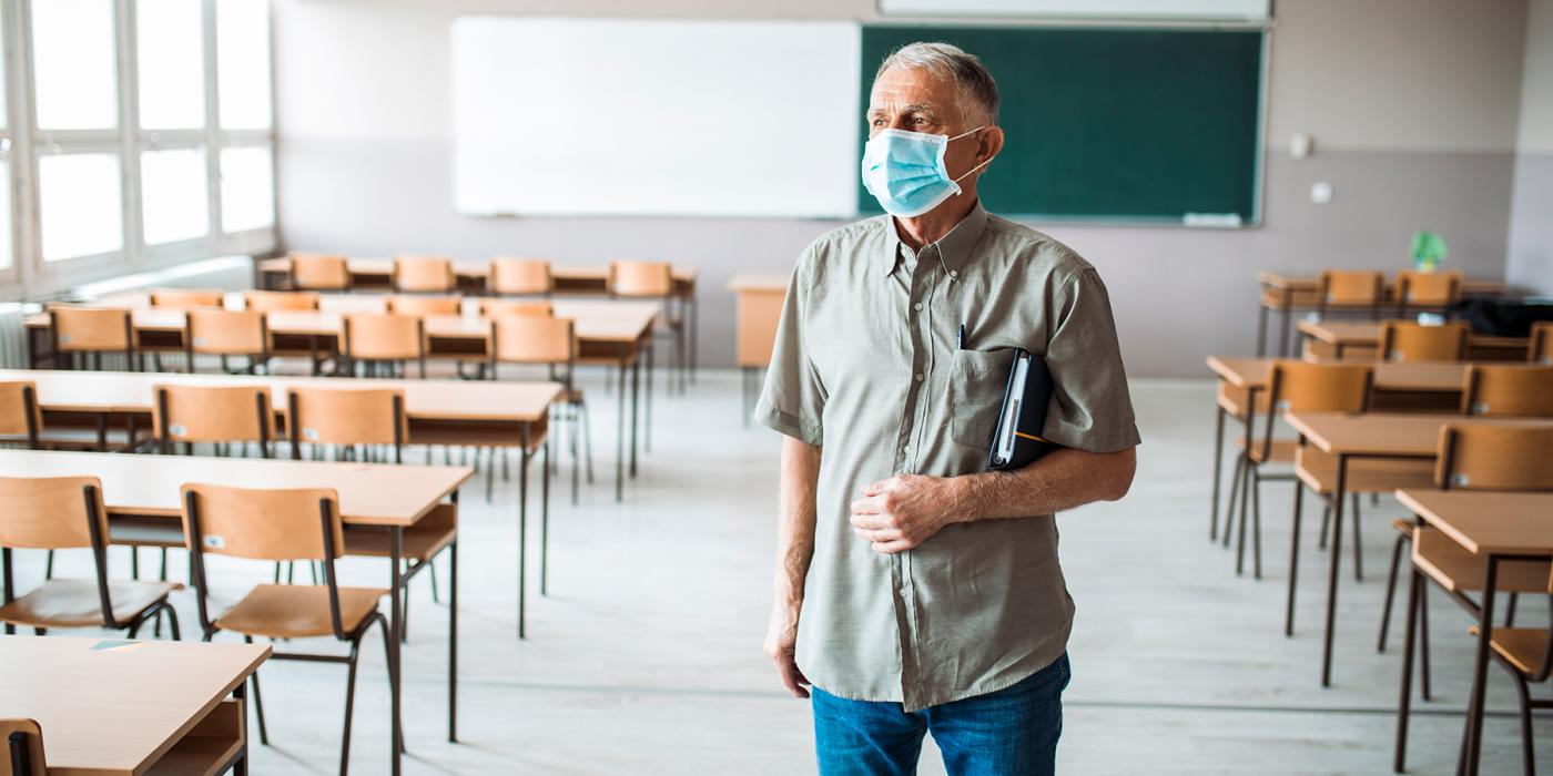 teacher wearing mask in empty classroom
