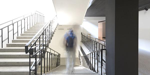 a student, not in focus, walks in a school building