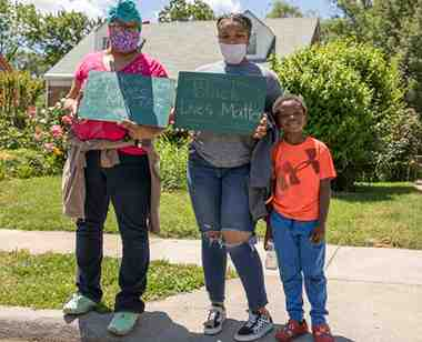 Family with BLM signs