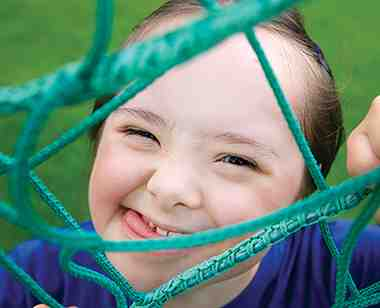 Child with downs syndrome makes a silly face while playing