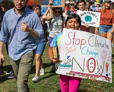 small girl holds sign at the climate change rally
