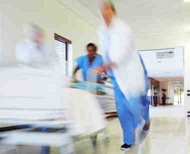 Emergency room medical staff rush by