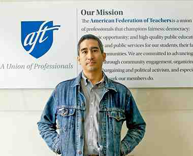 """A man, Jose Brito, stands in front of the AFT's """"Our Mission"""" sign."""
