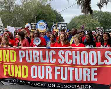 protesting educators hold sign that says fund public schools fund our future
